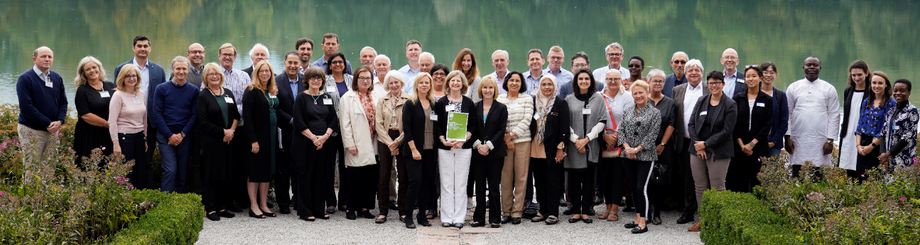Attendees of the Salzburg Global Forum standing in front of a lake.