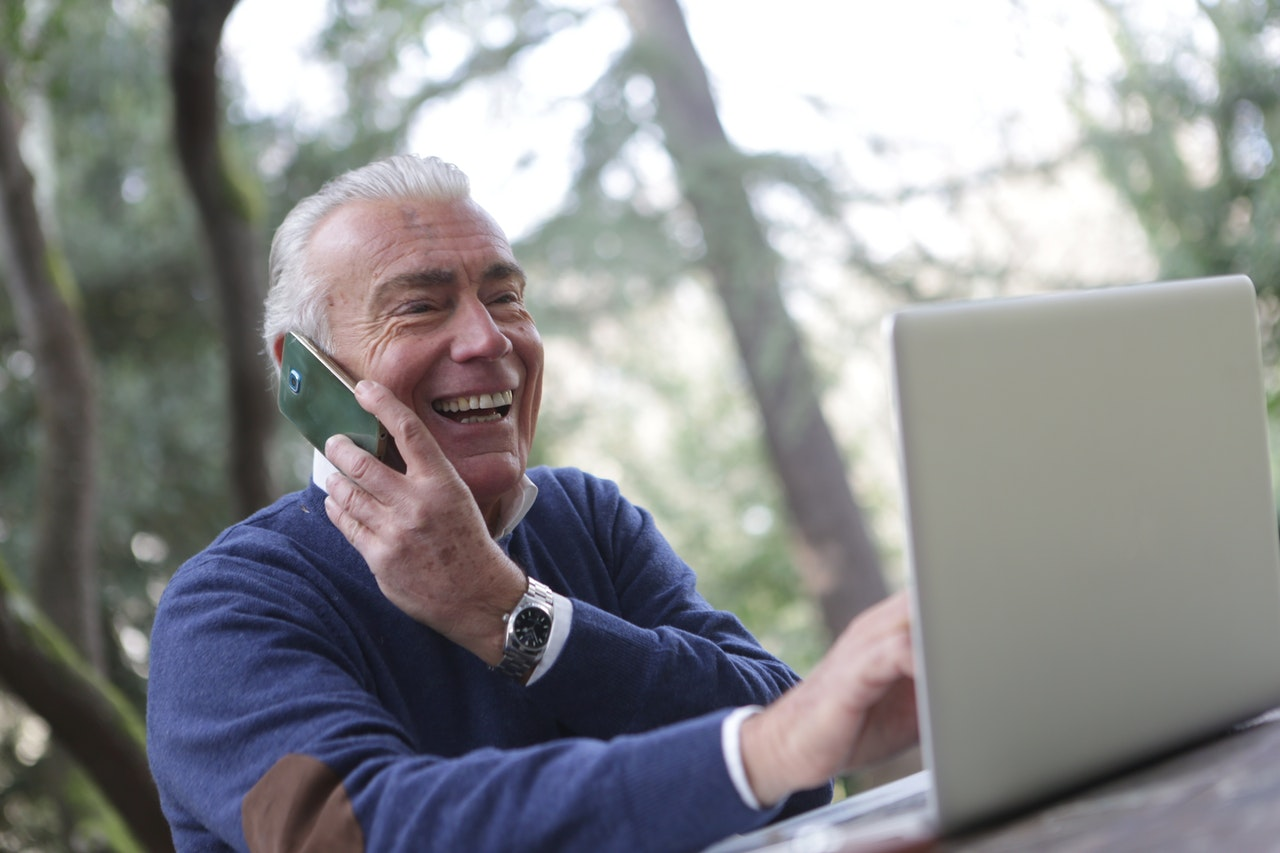 older man talking on phone while typing on computer