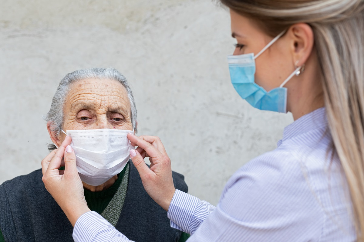 A personal care worker helps an older person put on a mask.