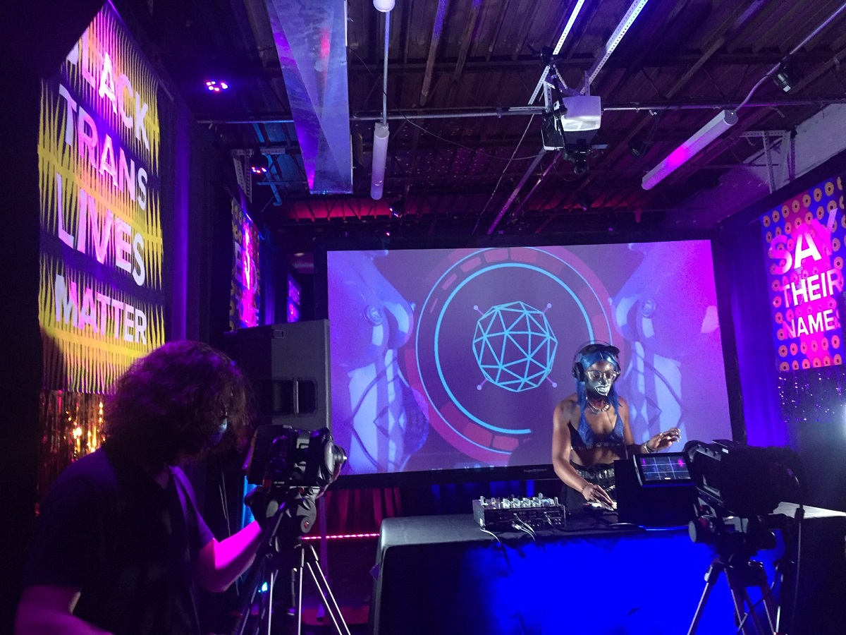 Kha'DJ, wearing long blue wig, head phones, and a mask, stands at a turntable playing music. Projector screens surround the DJ, displaying blue and purple lights and the sayings Black Trans Lives Matter and Say Their Names. To the left is a camera man working a camera that is recording the DJ.