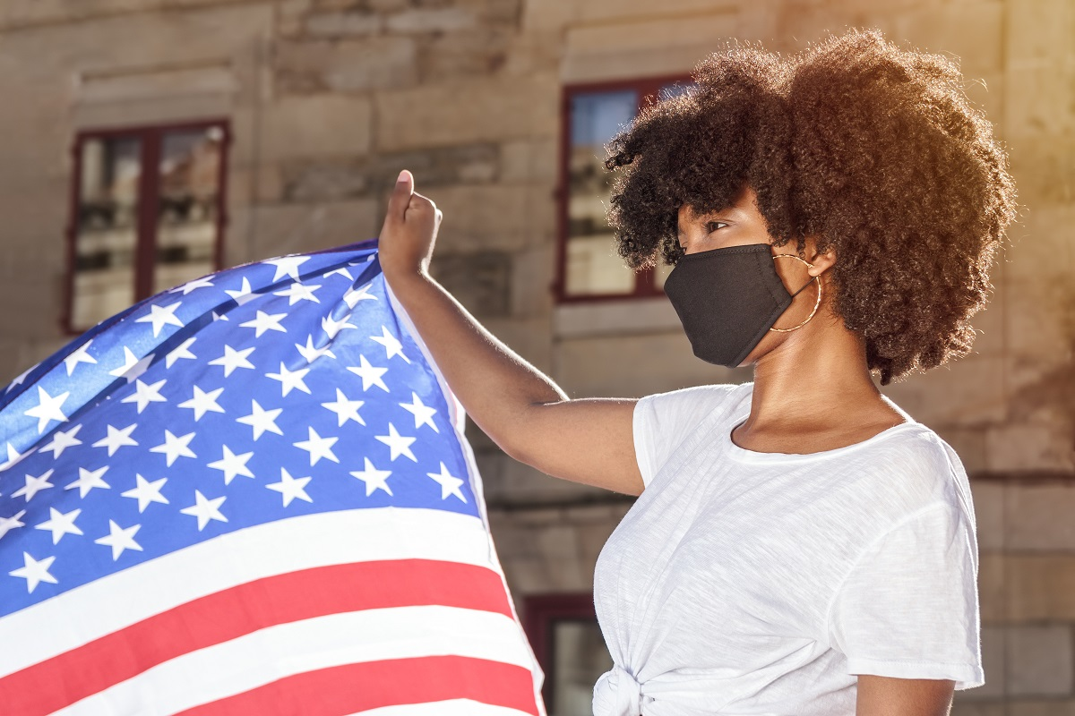 A woman with brown skin wears a black mask and holds an American flag.